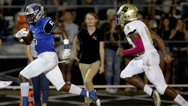 Bartram Trail defensive back Tre'Vez Johnson returns an interception for a touchdown as Nease quarterback Joe Nieves chases behind. Bartram won the game 52-22. (Ralph D. Priddy, Contributed photo)