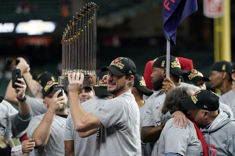 FILE - In this Oct. 30, 2019, file photo, Washington Nationals starting pitcher Max Scherzer celebrates with the trophy after Game 7 of the baseball World Series against the Houston Astros in Houston. The Nationals head to spring training with mostly the same squad that won the World Series. They are counting again on being led by a star-studded rotation featuring Scherzer and Stephen Strasburg, along with slugger Juan Soto. (AP Photo/David J. Phillip, File)
