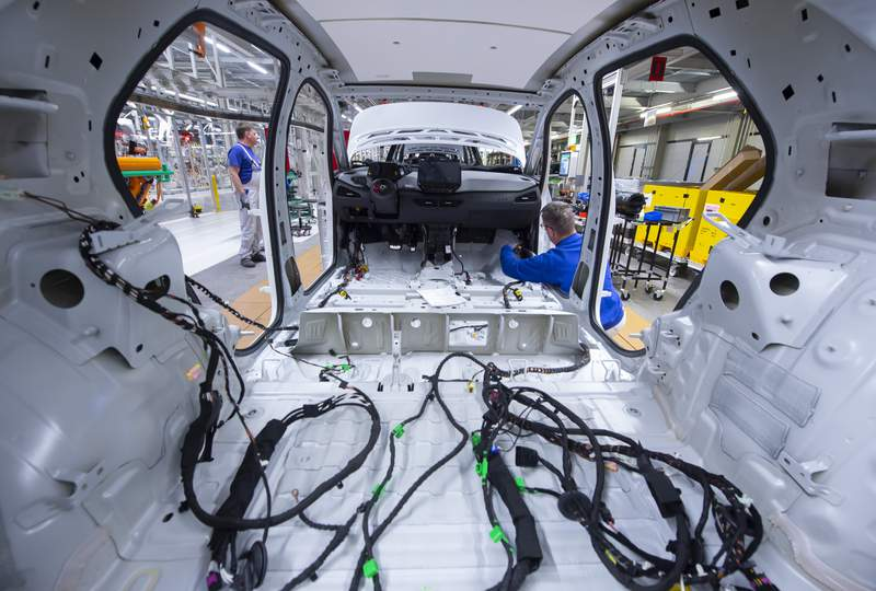 FILE - In this Tuesday, Feb. 25, 2020 file photo, a worker completes an electric car ID.3 body at the assembly line, during a press tour at the plant of the German manufacturer Volkswagen AG, VW, in Zwickau, Germany. Automaker Volkswagen tripled sales of battery-only cars last year as its new electric compact ID.3 came on the market ahead of tough new limits on auto emissions. (AP Photo/Jens Meyer, file)
