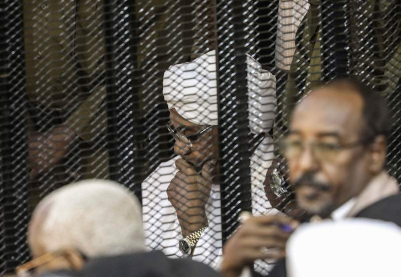 FILE - In this Aug. 24, 2019 file photo, Sudan's autocratic former President Omar al-Bashir sits in a cage during his trial on corruption and money laundering charges, in Khartoum, Sudan. A top Sudanese official said Monday, Feb. 11, 2020, that transitional authorities and rebel groups have agreed to hand over al-Bashir to the International Criminal Court for war crimes, including mass killings in Darfur. Since his ouster in April, al-Bashir has been in jail in Sudans capital, Khartoum over charges corruption and killing protesters. (AP Photo, File)