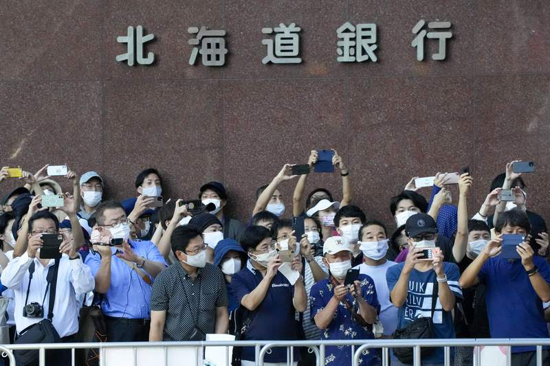 """FILE - In this Aug. 7, 2021, file photo, Spectators wearing face masks wait for competitors in the women's marathon at the 2020 Summer Olympics in Sapporo, northern Japan. Japan was set to expand its coronavirus state of emergency for a second week in a row Wednesday, Aug. 25, 2021, adding several more prefectures, including Hokkaido, as a surge in infections fueled by the delta variant strains the country's health care system.Japanese characters at top read: """"Hokkaido Bank."""" (AP Photo/Shuji Kajiyama, File)"""