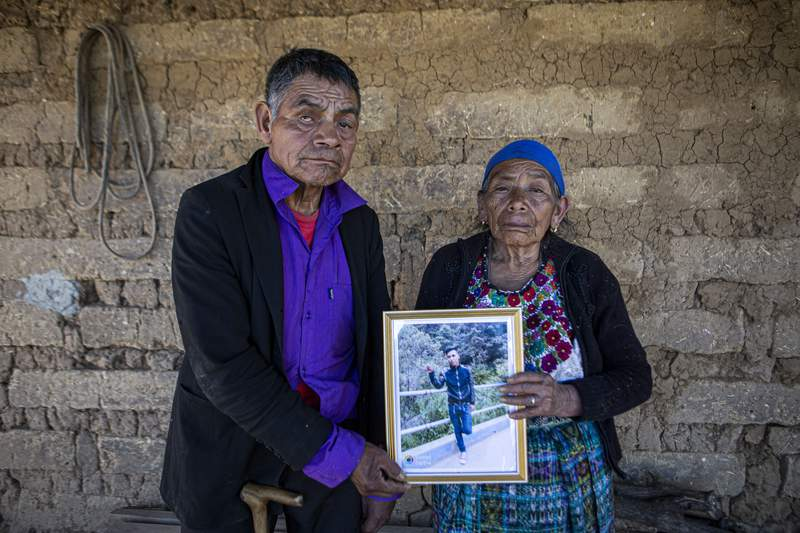 FILE - In this Jan. 27, 2021 file photo, German and Maria Tomas pose for a photo holding a framed portrait of their grandson Ivan Gudiel who they believe is one of the charred corpses found on a rural road on the Mexico-US border township of Camargo, at their home in Comitancillo, Guatemala. A dozen special operations officers have been ordered held for trial on charges they shot to death at least 14 Guatemalan migrants and two Mexicans on a rural road in the border township of Camargo. (AP Photo/Oliver de Ros, File)