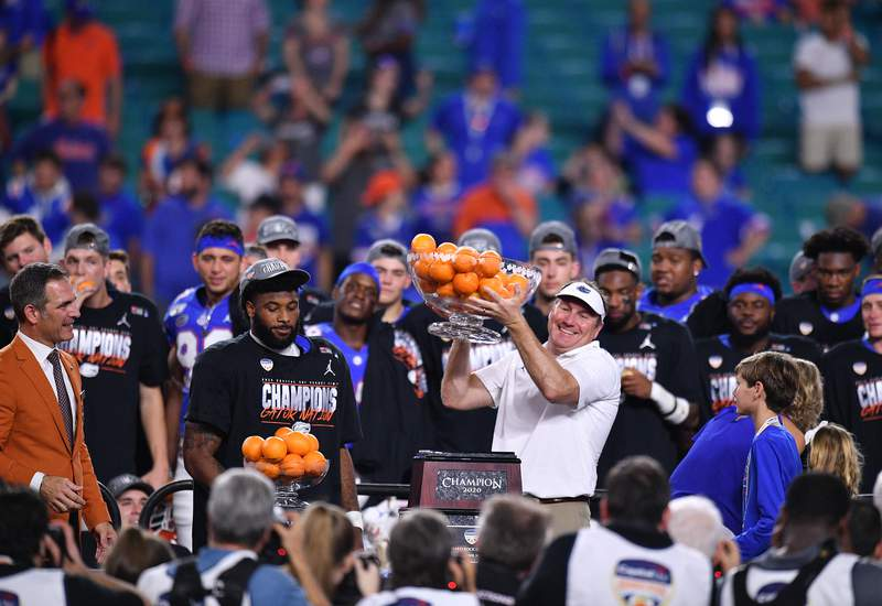 MIAMI, FLORIDA - DECEMBER 30: Head Coach Dan Mullen of the Florida Gators raises the Orange Bowl Trophy after winning the Capital One Orange Bowl against the Virginia Cavaliers at Hard Rock Stadium on December 30, 2019 in Miami, Florida. (Photo by Mark Brown/Getty Images)