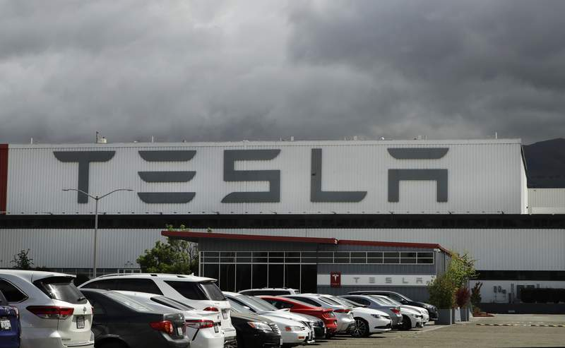 FILE - This May 12, 2020 file photo photo shows the Tesla plant in Fremont, Calif. Tesla is looking to raise up to $5 billion in capital through a stock offering as the electrical vehicle and solar panel maker seeks to take advantage of strong demand for its products.  (AP Photo/Ben Margot, File)