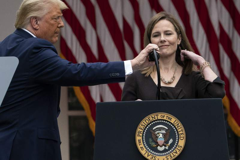 President Donald Trump adjusts the microphone after he announced Judge Amy Coney Barrett as his nominee to the Supreme Court, in the Rose Garden at the White House, Saturday, Sept. 26, 2020, in Washington. (AP Photo/Alex Brandon)