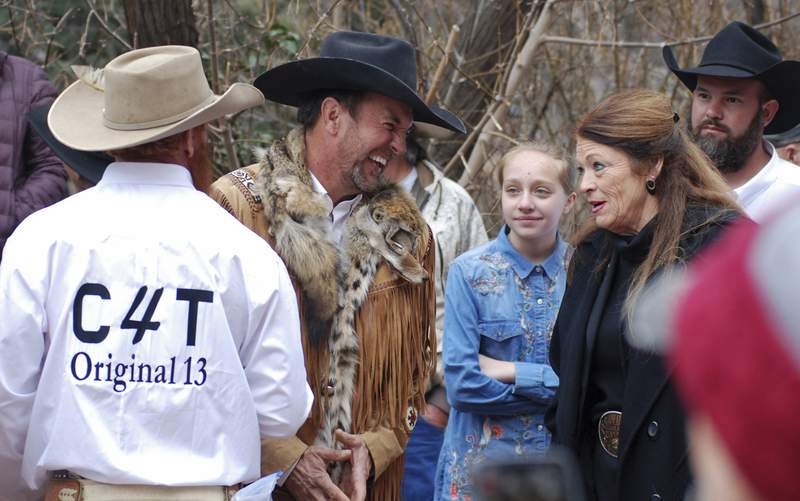 """FILE - In this March 12, 2019, file photo, Cowboys for Trump leader and Otero County Commissioner Couy Griffin, center, talks with Republican New Mexico state Rep. Candy Ezzell of Roswell, N.M., at a protest against gun control and pro-abortion rights legislation outside the New Mexico State Capitol, in Santa Fe, N.M. A New Mexico county official who runs a group called """"Cowboys for Trump"""" who had vowed to return to Washington after last week's riot at the U.S. Capitol to place a flag on House Speaker Nancy Pelosi's desk was arrested by the FBI on Sunday, Jan. 17, 2021. Griffin was arrested on charges of illegally entering the U.S. Capitol. (AP Photo/Morgan Lee, File)"""