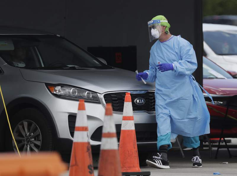 A health care worker walks around a car to test a passenger at a drive-through COVID-19 testing site outside Hard Rock Stadium, Wednesday, July 8, 2020, in Miami Gardens, Fla. (AP Photo/Wilfredo Lee)