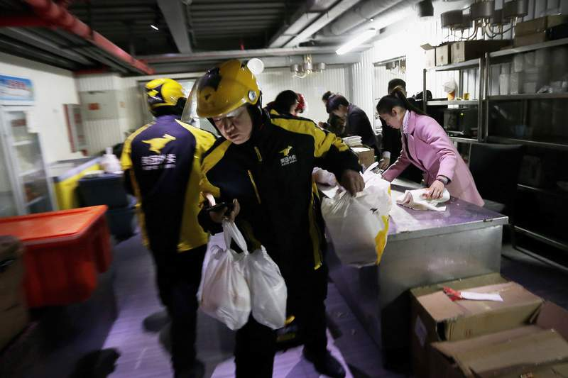 FILE - In this March 1, 2016, file photo, food delivery workers from Meituan, an E-commerce company, prepare to deliver orders placed online from a center in Beijing. Chinese food delivery giant Meituan said this week it raised nearly $10 billion in a sale of convertible bonds and additional shares and plans to invest those funds in developing and expanding delivery technologies. (AP Photo/Andy Wong, File)