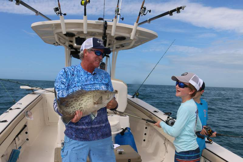 Capt Don Dingman and young angler Taylan share a smile over a Gag grouper he just reeled in on Hook The Future