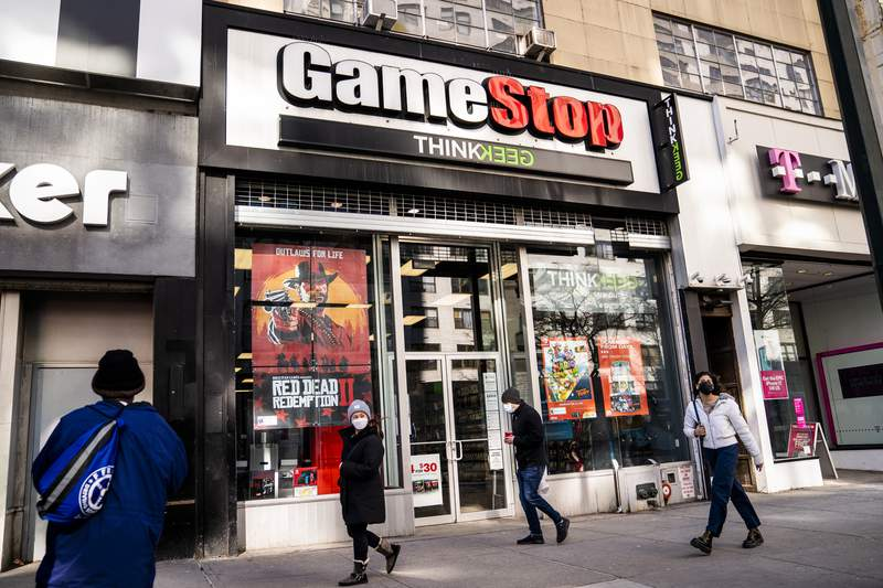 FILE - Pedestrians pass a GameStop store on 14th Street at Union Square, Thursday, Jan. 28, 2021, in the Manhattan borough of New York.  GameStop and a handful of other stocks whose meteoric rise last month shocked Wall Street began falling back to Earth this week. But the campaign that briefly pushed GameStop up by 1,600% at the expense of hedge funds that were betting it would lose value, known as shorting, could be a blueprint for similar efforts with other companies shares, some analysts say.   (AP Photo/John Minchillo, File)