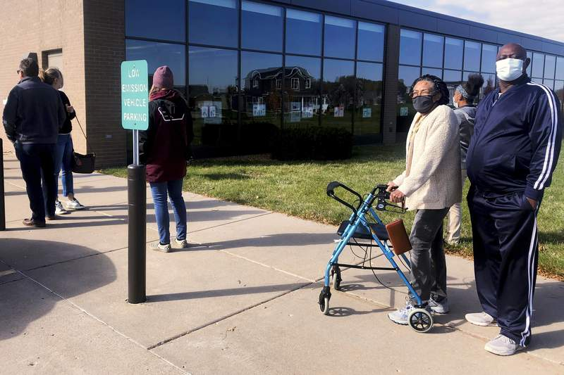 FILE - In this Oct. 30, 2020, file photo Lenore Benton-Bey, with a walker, and her husband, Charles Benton-Bey, wait in line with others to cast early votes at the Eastern Avenue Branch of the Davenport Public Library in Davenport, Iowa. (AP Photo/Geoff Mulvihill, File)