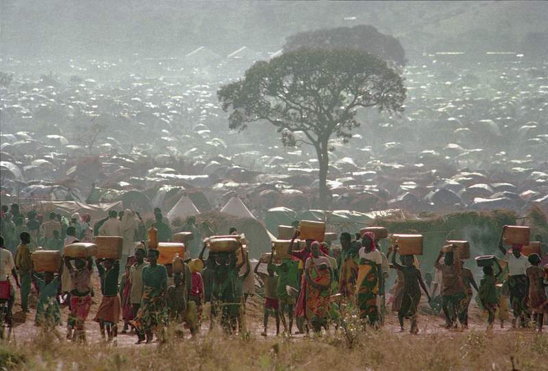 """FILE - In this Tuesday, May 17, 1994 file photo, refugees who fled the ethnic bloodbath in neighboring Rwanda carry water containers back to their huts at the Benaco refugee camp in Tanzania, near the border with Rwanda. A report commissioned by the Rwandan government due to be made public on Monday, April 19, 2021 concludes that the French government bears """"significant"""" responsibility for """"enabling a foreseeable genocide"""" that left more than 800,000 dead in 1994 and that that France """"did nothing to stop"""" the massacres. (AP Photo/Karsten Thielker, File)"""