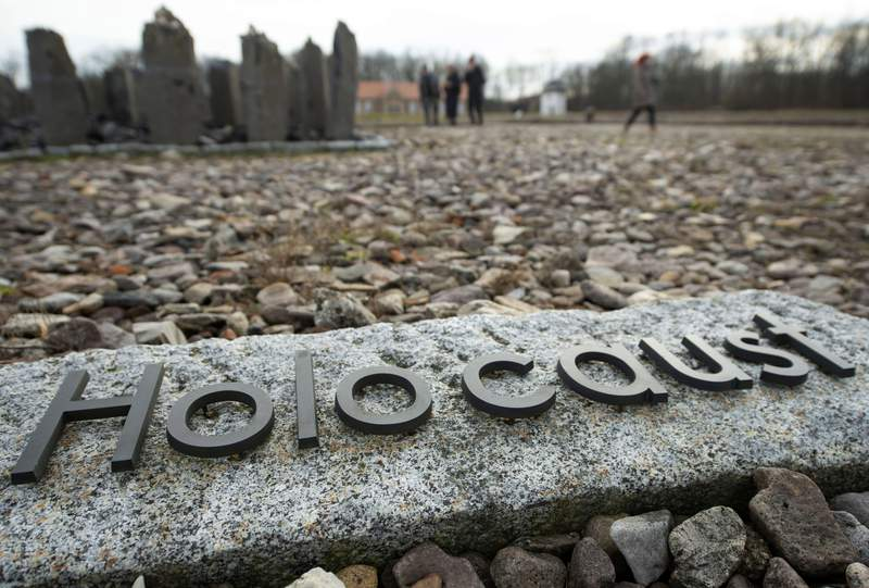 FILE - In this Monday, Jan. 27, 2020 file photo people walk behind the writing 'Holocaust' during the international Holocaust remembrance day in the former the Nazi concentration camp Buchenwald near Weimar, Germany. Friedrich Karl Berger, a 95-year-old former Nazi concentration camp guard, was deported to his native Germany on orders from a Tennessee court.  (AP Photo/Jens Meyer, file)