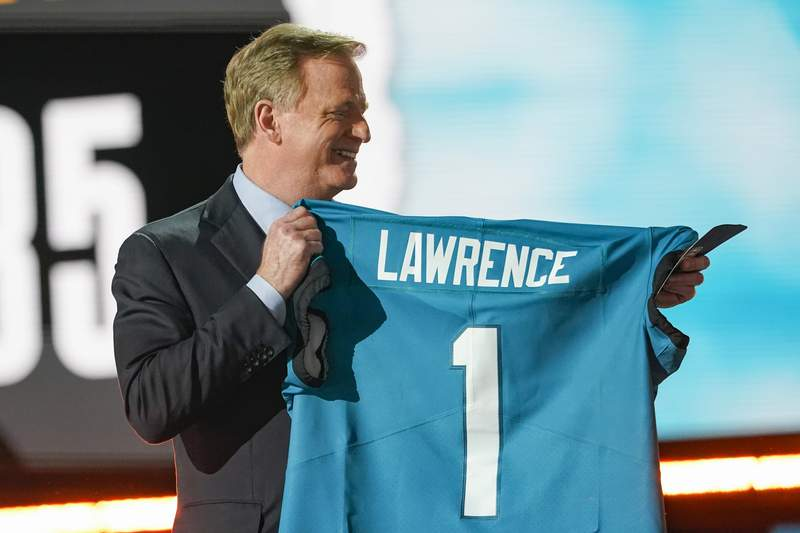NFL commissioner Roger Goodell holds a Jacksonville Jaguars jersey as he announces that the Jaguars had chosen Clemson quarterback Trevor Lawrence with the first pick in the NFL football draft, Thursday April 29, 2021, in Cleveland. (AP Photo/Tony Dejak)