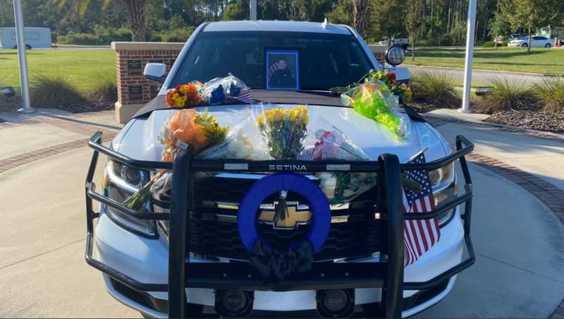Flowers decorate the hood of fallen Deputy Joshua Moyers' cruiser.