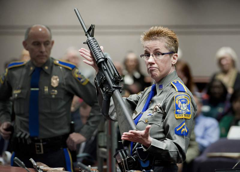 FILE - In this Jan. 28, 2013, file photo, firearms training unit Detective Barbara J. Mattson, of the Connecticut State Police, holds up a Bushmaster AR-15 rifle made by Remington Arms, the same make and model of the gun used by Adam Lanza in the December 2012 Sandy Hook School shooting, during a hearing of a legislative subcommittee in Hartford, Conn. On Tuesday, Aug. 18, 2020, a lawyer for some of the Sandy Hook school shooting victims accused Remington Arms of using its new bankruptcy case to try to wipe out the families' lawsuit against the company over how it marketed the rifle used in the massacre. (AP Photo/Jessica Hill, File)
