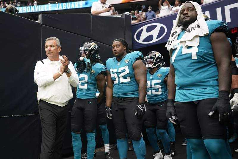 Jacksonville Jaguars coach Urban Meyer, left, prepares to lead his team onto the field before an NFL football game against the Houston Texans Sunday, Sept. 12, 2021, in Houston. (AP Photo/Sam Craft)