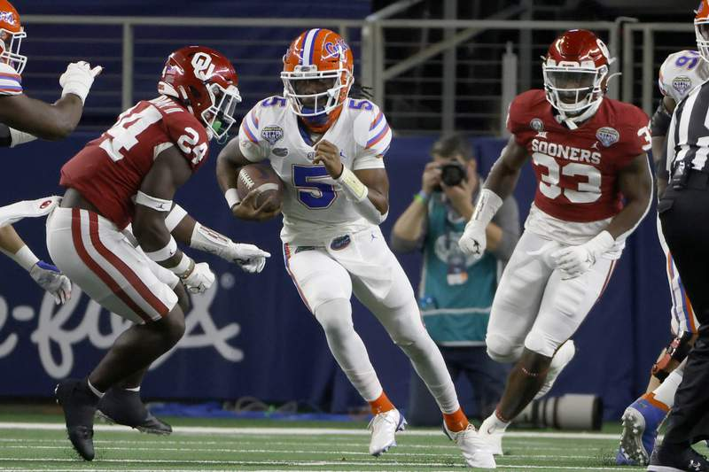 Florida quarterback Emory Jones (5) runs the ball as Oklahoma linebacker Brian Asamoah (24) and defensive end Marcus Stripling (33) give chase during the first half of the Cotton Bowl NCAA college football game in Arlington, Texas, Wednesday, Dec. 30, 2020. (AP Photo/Ron Jenkins)