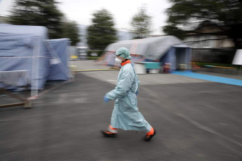 FILE - In this Thursday, March 12, 2020 file photo, a worker wearing a mask and protective clothing walks between the emergency structures that were set up to ease procedures at the Brescia hospital in northern Italy. The medical impact of the new coronavirus is coming into sharper focus in March 2020 as it continues its spread in what is now officially recognized as a pandemic. (AP Photo/Luca Bruno)