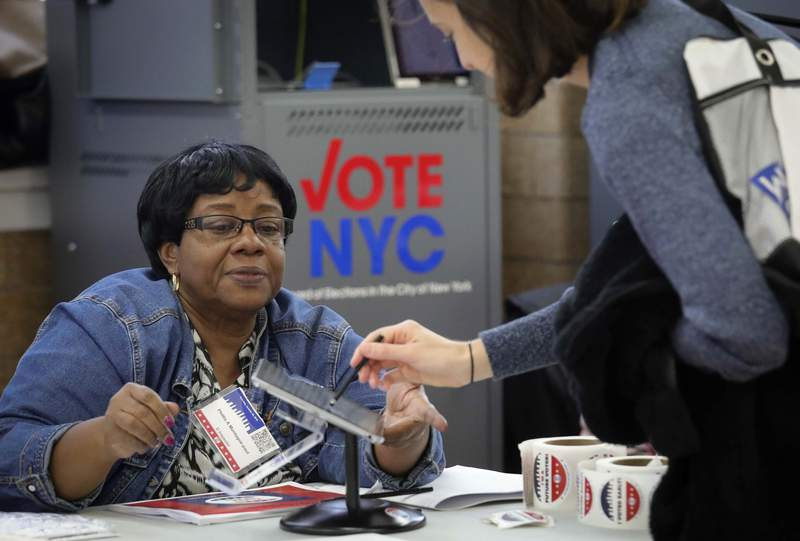 FILE - In this Oct. 26, 2019, file photo, a polling site inspector processes a voter using the new E-Poll Book tablet, during early voting at Brooklyn's Clara Barton High School in New York. Electronic poll books are computer software used in polling places on Election Day. The software allows election inspectors to look up a voters registration record, confirm the registration is correct and assign a ballot to that voter. (AP Photo/Bebeto Matthews, File)