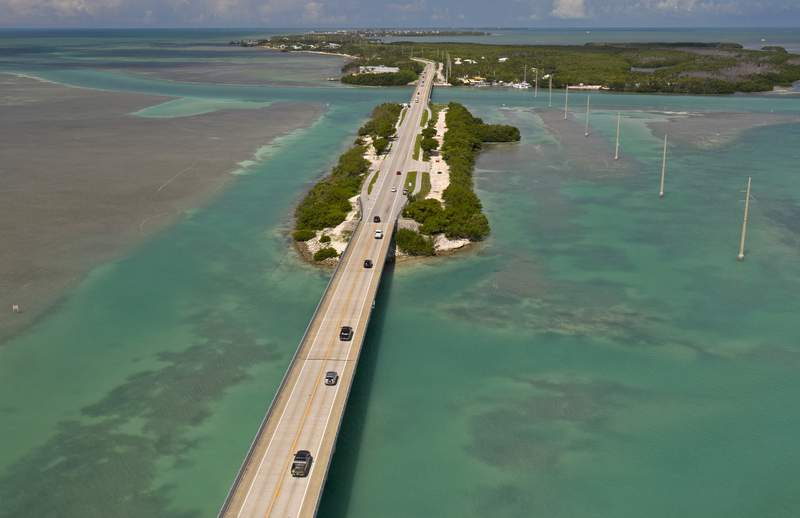 In this drone aerial photo provided by the Florida Keys News Bureau, traffic flows on the Florida Keys Overseas Highway in Islamorada, Fla., towards Key West Monday, June 1, 2020. After being closed to visitors since March 22, 2020, to help curtail the spread of COVID-19, the Florida Keys reopened to tourists Monday. Tourism employs about 45 percent of the Keys workforce. (Andy Newman/Florida Keys News Bureau via AP)