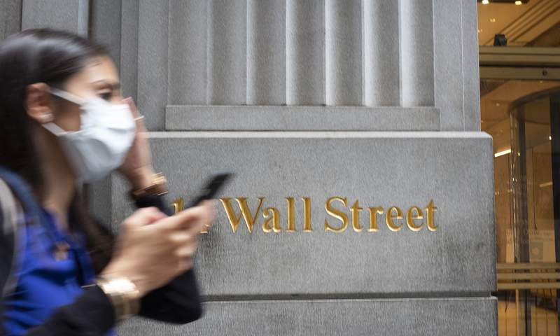 FILE - In this June 30, 2020 file photo, a woman wearing a mask passes a sign for Wall Street during the coronavirus pandemic. The S&P 500 is trading above its record closing high Wednesday, Aug. 12,  after a rebound for stocks helped the index erase the last of the historic losses taken due to the pandemic. The index was up 1.6% in afternoon trading, with big technology stocks once again leading the way.   (AP Photo/Mark Lennihan, File)