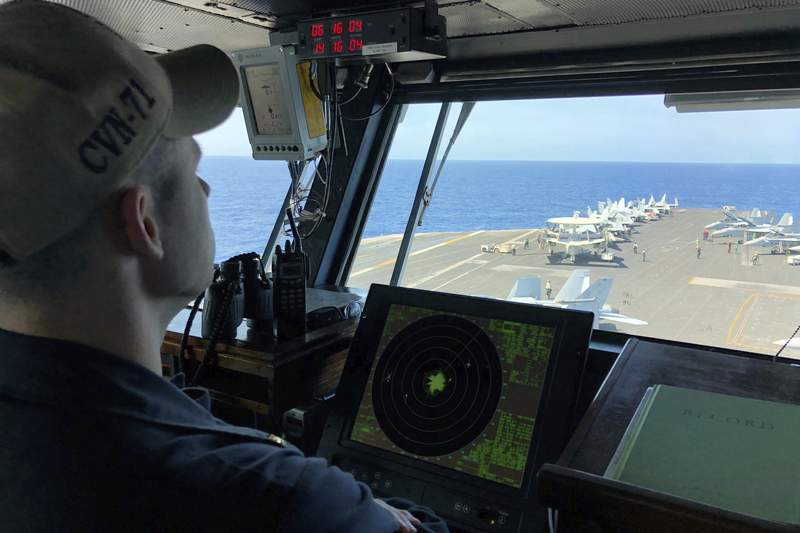 FILE - In this April 10, 2018, file photo, a U.S. Navy crewman monitors on the deck of the U.S. aircraft carrier Theodore Roosevelt in international waters off South China Sea. The USS Theodore Roosevelt made the second-ever visit by a U.S. aircraft carrier strike group to Vietnam to mark 25 years of diplomatic relations and growing security ties between the former Cold War antagonists amid China's aggressive moves in the South China Sea.  (AP Photo/Jim Gomez, File)