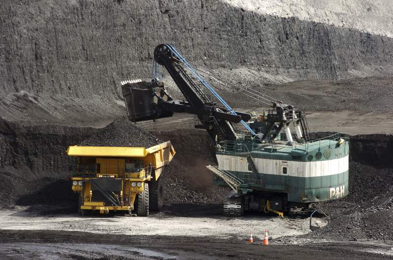 FILE - In this April 4, 2013, file photo, a mechanized shovel loads a haul truck with coal at the Spring Creek coal mine near Decker, Mont. A judge says U.S officials downplayed the climate change impacts and other environmental costs from the expansion of a massive coal mine near the Montana-Wyoming border, in a case that could show how far the Biden administration is willing to go to unwind his predecessors' decisions. (AP Photo/Matthew Brown, File)
