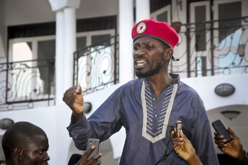 FILE - In this Thursday, May 2, 2019 file photo, Ugandan pop star and opposition politician Bobi Wine, whose real name is Kyagulanyi Ssentamu, greets his followers as he arrives home after being released from prison on bail in Kampala, Uganda. Police on Tuesday, Nov. 3, 2020 again arrested Bobi Wine, dragging him from his car and putting him in a police van, just after he was successfully certified as a candidate in next year's election. (AP Photo/Ronald Kabuubi, File)