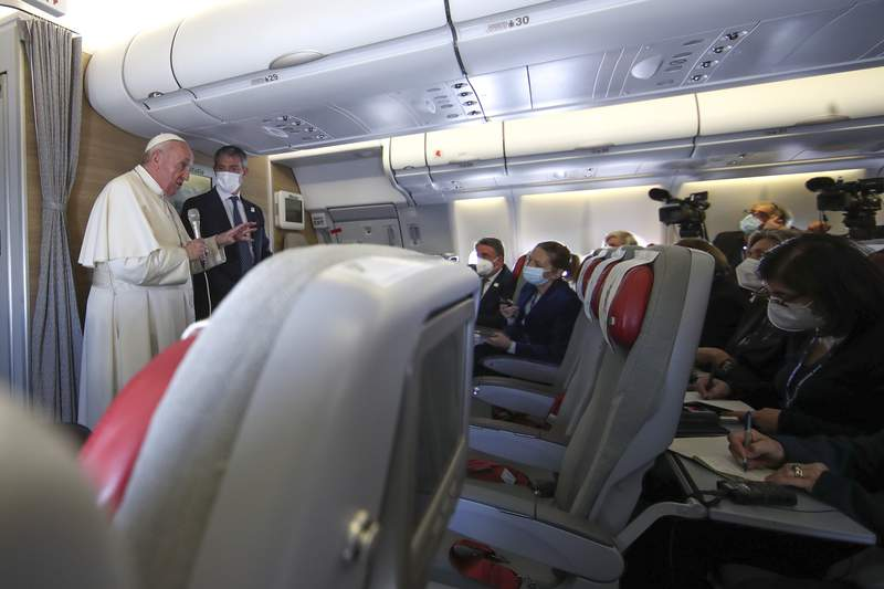 Pope Francis speaks to journalists, Monday, March 8, 2021, while flying back to The Vatican at the end of his four-day trip to Iraq where he met with different Christian communities and Shiite revered cleric Grand Ayatollah Ali al-Sistani. (AP Photo/Yara Nardi, pool)