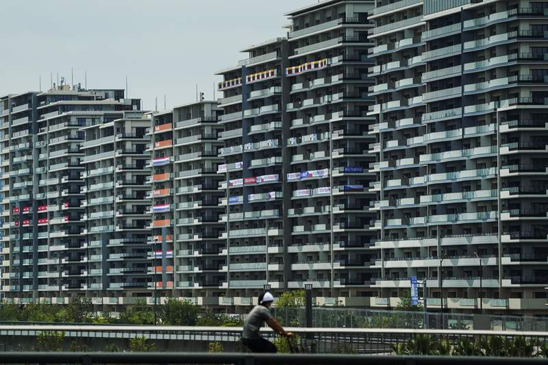 A man rides his bike near the athlete's village for the 2020 Summer Olympics and Paralympics, Thursday, July 15, 2021, in Tokyo. (AP Photo/Jae C. Hong)