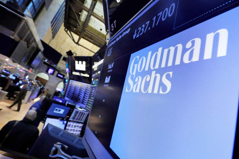 FILE - In this Dec. 13, 2016, file photo, the logo for Goldman Sachs appears above a trading post on the floor of the New York Stock Exchange. Goldman Sachs said its profits more than doubled from a year earlier thanks to a surge in both trading and advising revenue. (AP Photo/Richard Drew, File)