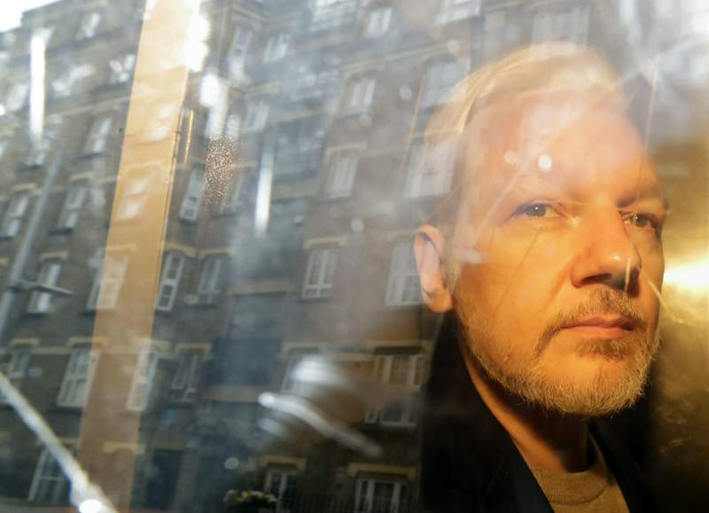 FILE - In this Wednesday May 1, 2019 file photo, buildings are reflected in the window as WikiLeaks founder Julian Assange is taken from court, where he appeared on charges of jumping British bail seven years ago, in London. WikiLeaks founder Julian Assange will find out Monday Jan. 4, 2021, whether he can be extradited from the U.K. to the U.S. to face espionage charges over the publication of secret American military documents. (AP Photo/Matt Dunham, File)
