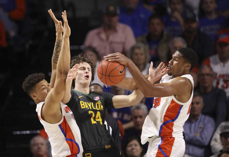 Florida forward Kerry Blackshear Jr. (24) steals the ball from Baylor guard Matthew Mayer (24) as he is defended by Florida forward Keyontae Johnson (11) during the first half of an NCAA college basketball game Saturday, Jan. 25, 2020, in Gainesville, Fla. (AP Photo/Matt Stamey)