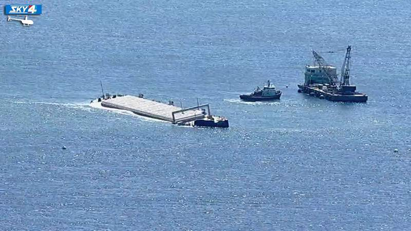 Crane and tug boats continue operations around stranded barge.