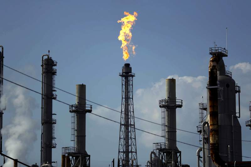 FILE - In this Thursday, Aug. 31, 2017, file photo, a flame burns at the Shell Deer Park oil refinery in Deer Park, Texas. Oil prices are plunging Sunday, March 8, 2020, amid worries that an OPEC dispute will lead a virus-weakened economy to be awash in an oversupply of crude. (AP Photo/Gregory Bull, File)