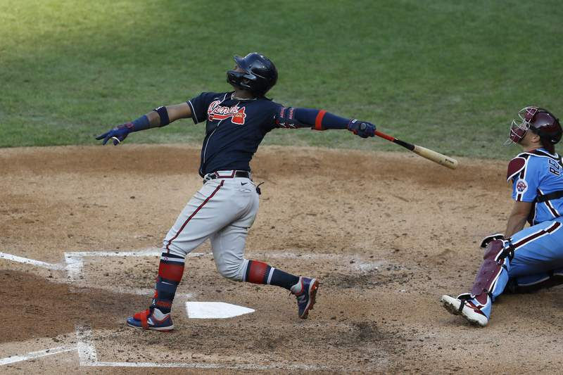 Atlanta Braves' Ronald Acuna Jr. follows through after hitting a home run off Philadelphia Phillies pitcher Spencer Howard during the fifth inning of the second baseball game in a doubleheader, Sunday, Aug. 9, 2020, in Philadelphia. (AP Photo/Matt Slocum)